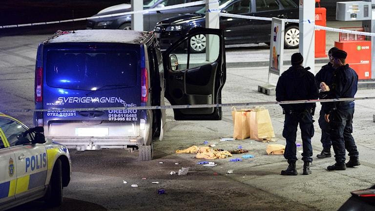 Polis och avspärringar kring den beskjutna minibussen i Fittja. Foto: TT