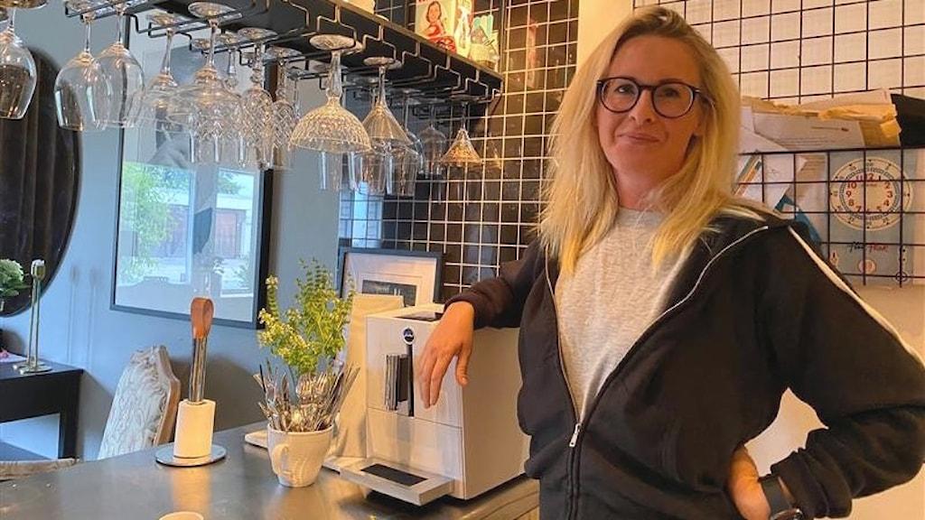Kvinna lutar sig mot en kaffemaskin