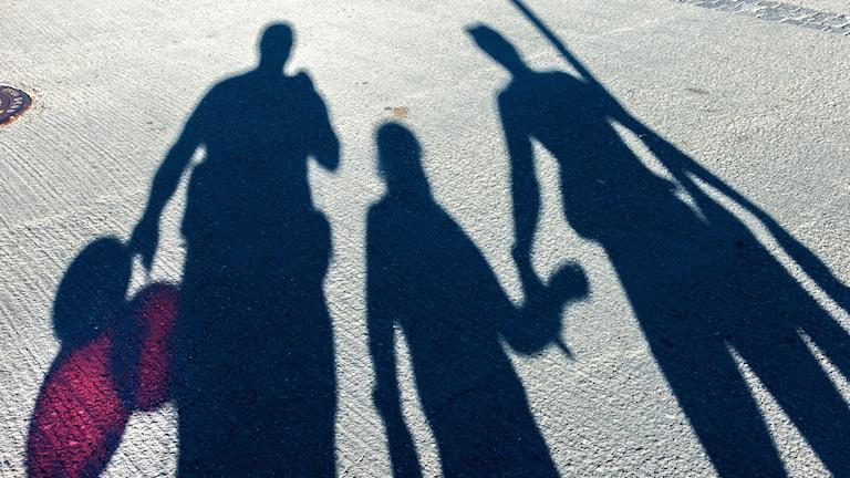 Skuggan av familj två vuxtan och ett barn