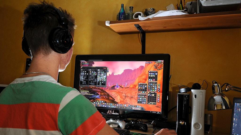 En tonårspojke spelar dataspel.