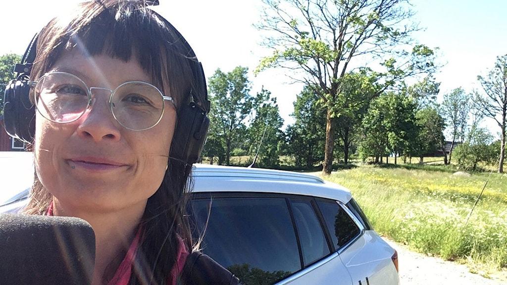 En kvinna står utomhus och tittar in i kameran. På huvudet har hon hörlurar och hon håller i en mikrofon.