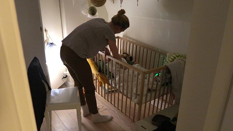 Äiti kumartuneena pinnasängyssä olevan vauvan ylle.