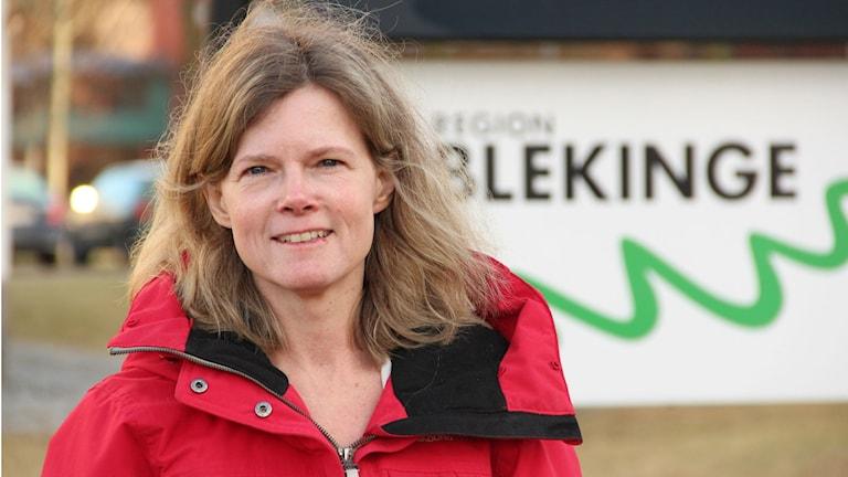 En kvinna i röd jacka står framför en skylt där det står Region Blekinge. Foto: Rebecka Gyllin/Sveriges Radio