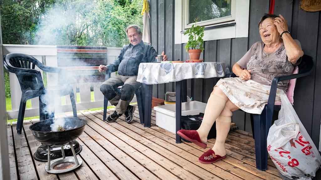En äldre kvinna och äldre man sitter på sin altan. Framför sig har dem en klotgrill med brinnande enris.