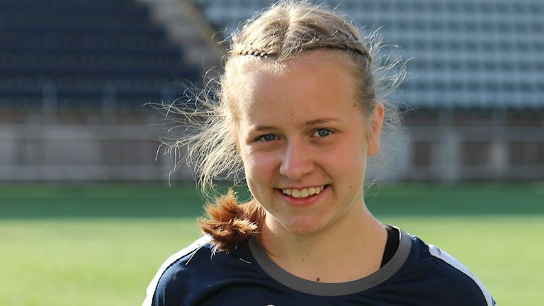 Porträttbild av Wilma Ritzén med fotbollsplan och läktare i bakgrunden.