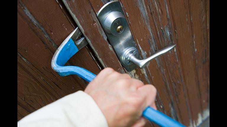En inbrottstjuv bryter upp dörren till en bostad med hjälp av en kofot Foto: Henrik Montgomery / SCANPIX