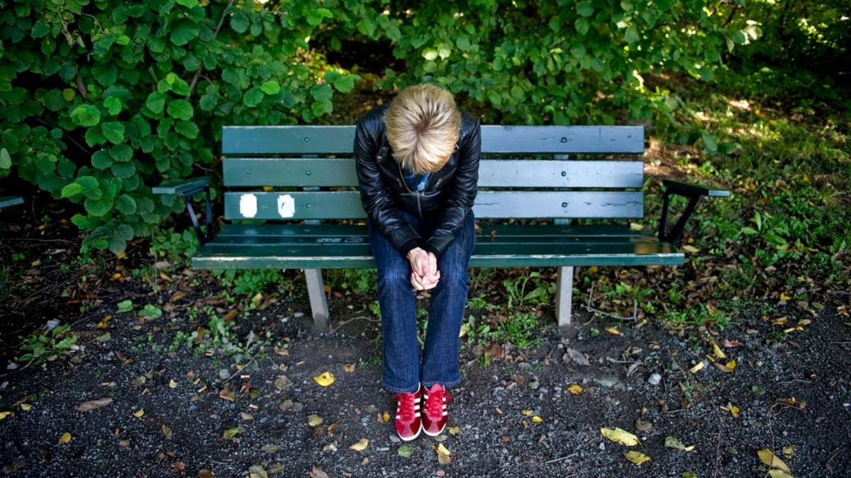 Kvinna sitter ensam på bänk. Foto: Jessica Goe/TT