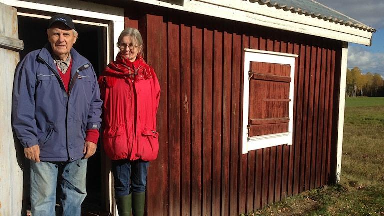 Erik Nilsson och Gunilla Larsson utanför sockensamisk stuga på Storön på Långsjön. Foto: Jörgen Heikki, SR Sameradion & SVT Sápmi.
