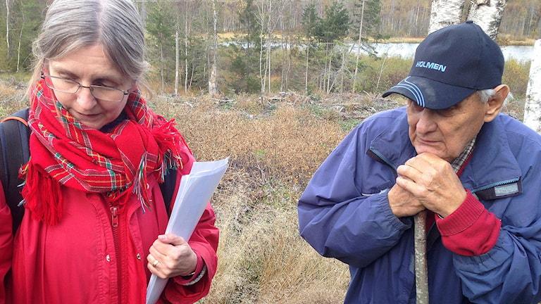 Gunilla Larsson och Erik Nilsson studerar lämningen efter en samisk stuga vid Medkogstjärn, Hudiksvall. Foto: Jörgen Heikki/ Sameradion & SVT Sápmi.
