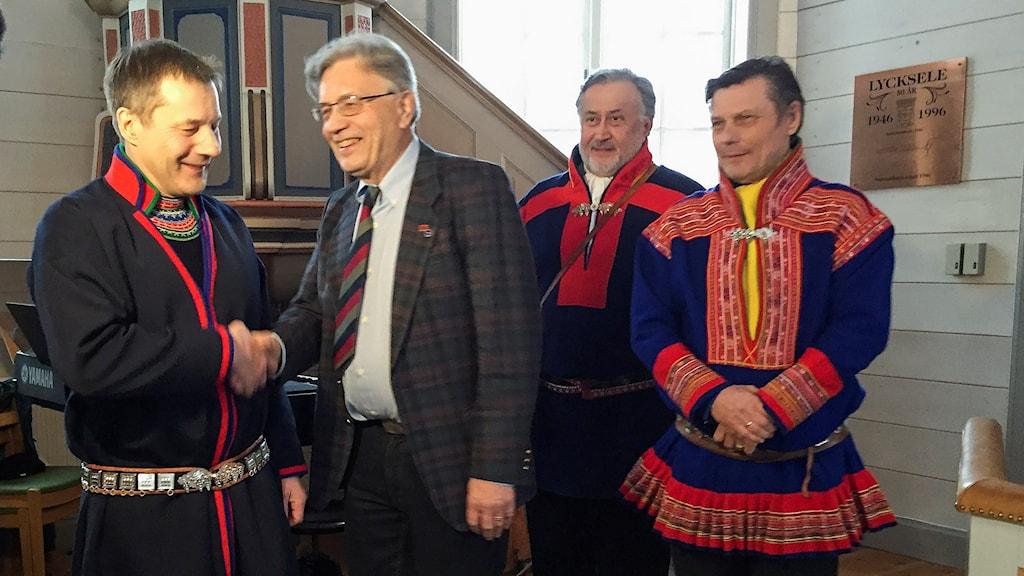 Henrik Barruk skakar hand med Olavi Korhonen, Pekka Sammallahti och Ole Henrik Magga.