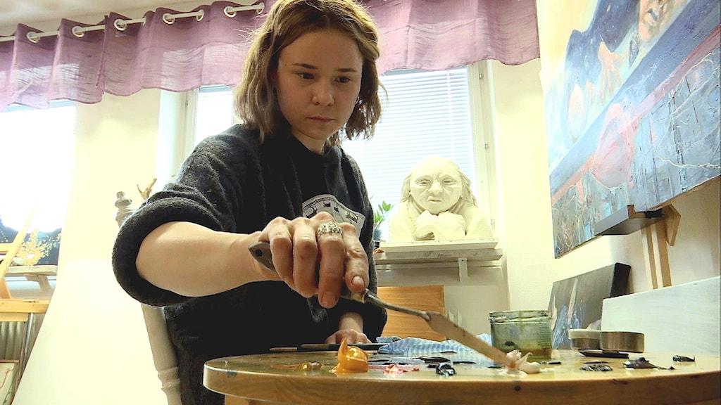 Konstnären Inga Wiktoria Påve blandar färgerna med en paljettkniv.