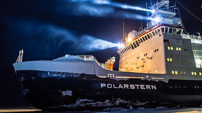 Isbrytaren Polarstern med svart skrov och vit överbyggnad på isigt hav och starka strålkastare.