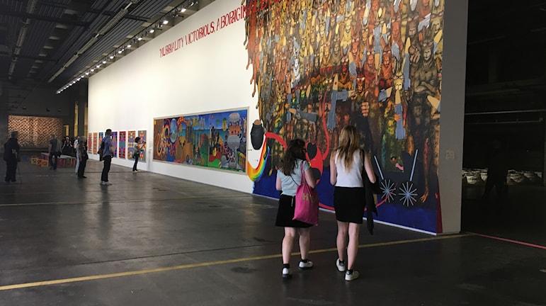Gordon Hookeys muralmålning Murriland på Documenta14, i bakgrunden syns verk av Máret Anne Sara.