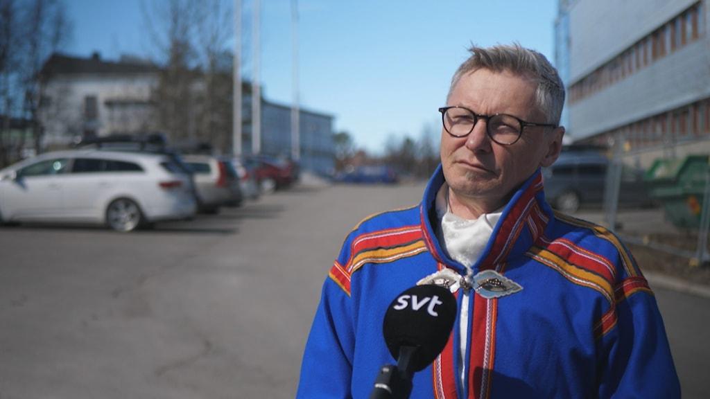 Per-Olof Nutti i blå gákti på en parkering med kontorsbyggnad i bakgrunden. solsken, mikrofon framför