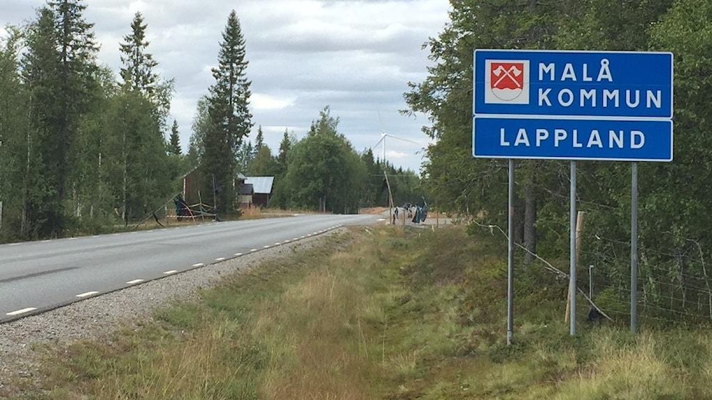Bredvid vägen står en skylt som visar att här går gränsen till Malås kommun och Lapplands landskap.