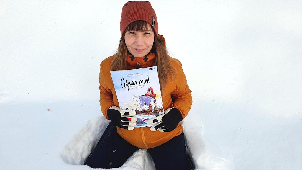 En kvinna sitter i snön med en bok.