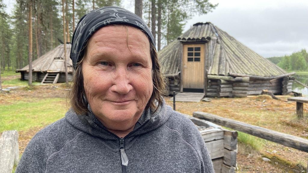 Lotta Svensson framför två träkåtor