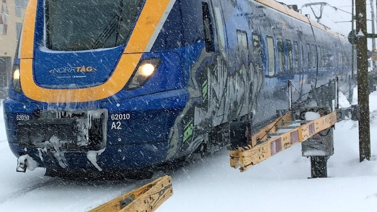 Ett tåg rullar genom ett snöigt Sundsvall.