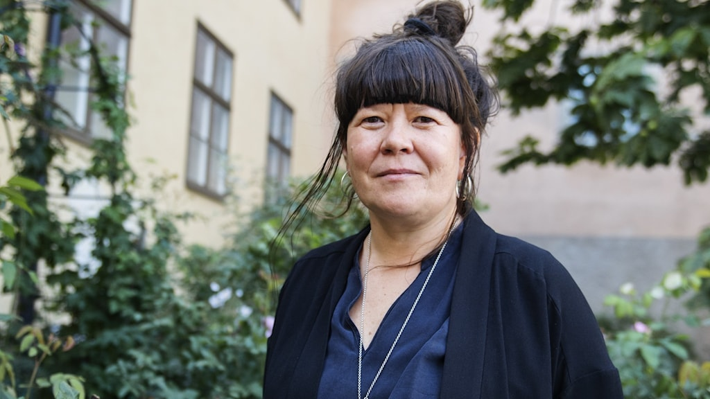 Patricia Fjellgren står i en blomstrande trädgård med svart kofta och knut på huvudet.