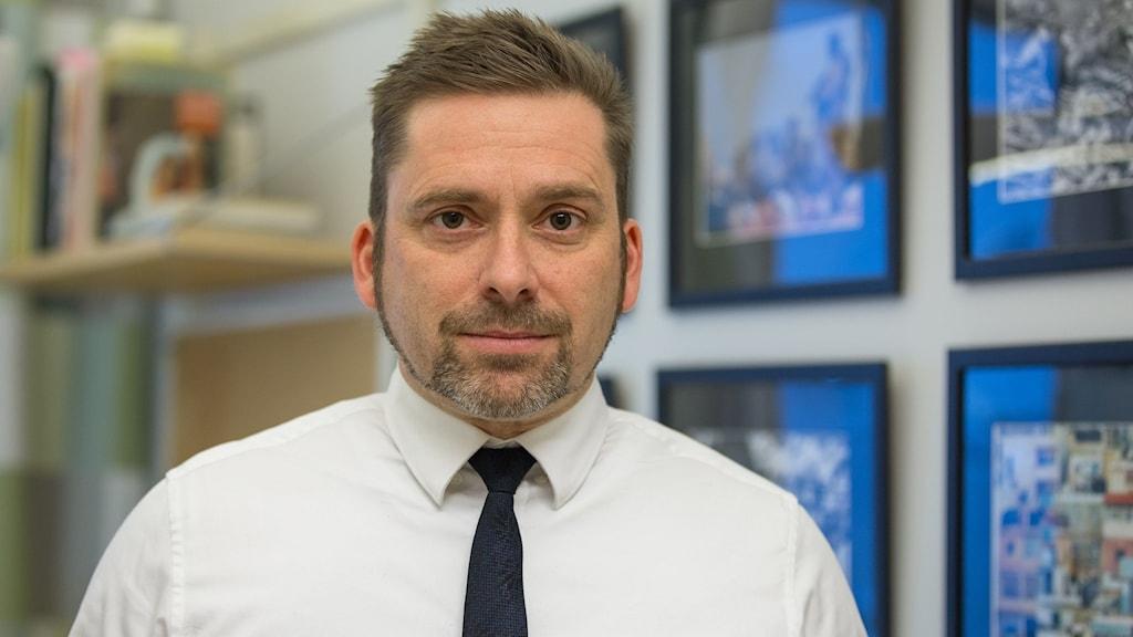 Erik Törnlund står i ett kontorsrum, i förgrunden finns en bokhylla och på väggen han står framför hänger fyra inramade foton.
