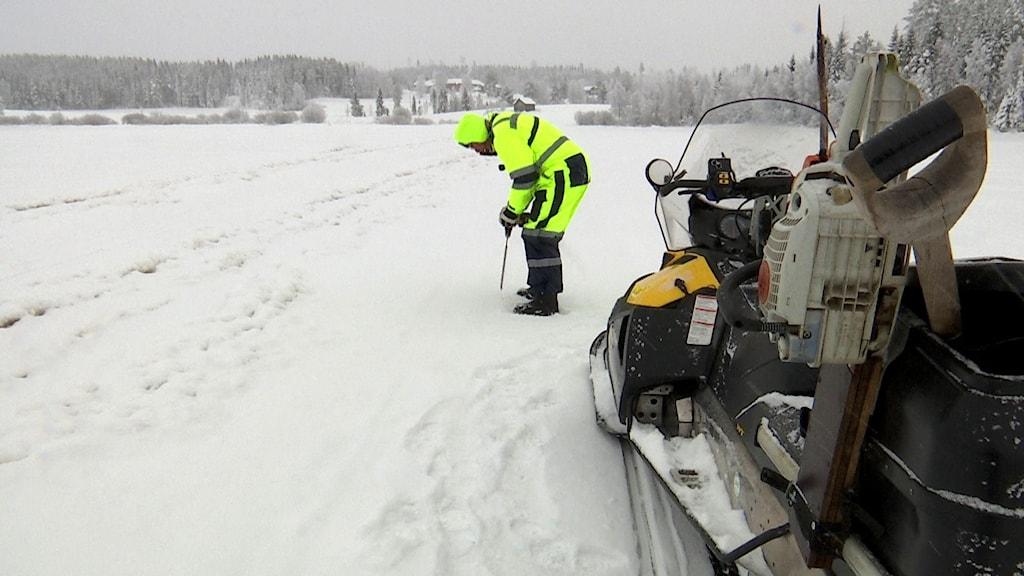 Skoterförare borrar i isen för att se isens  tjocklek.