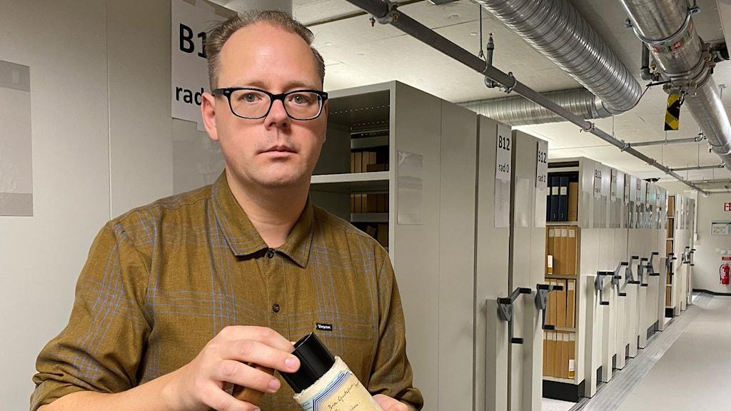 Wictor Johansson, forskningsarkivare, Svenskt visarkiv, med en av Karl Tiréns vaxrullar.
