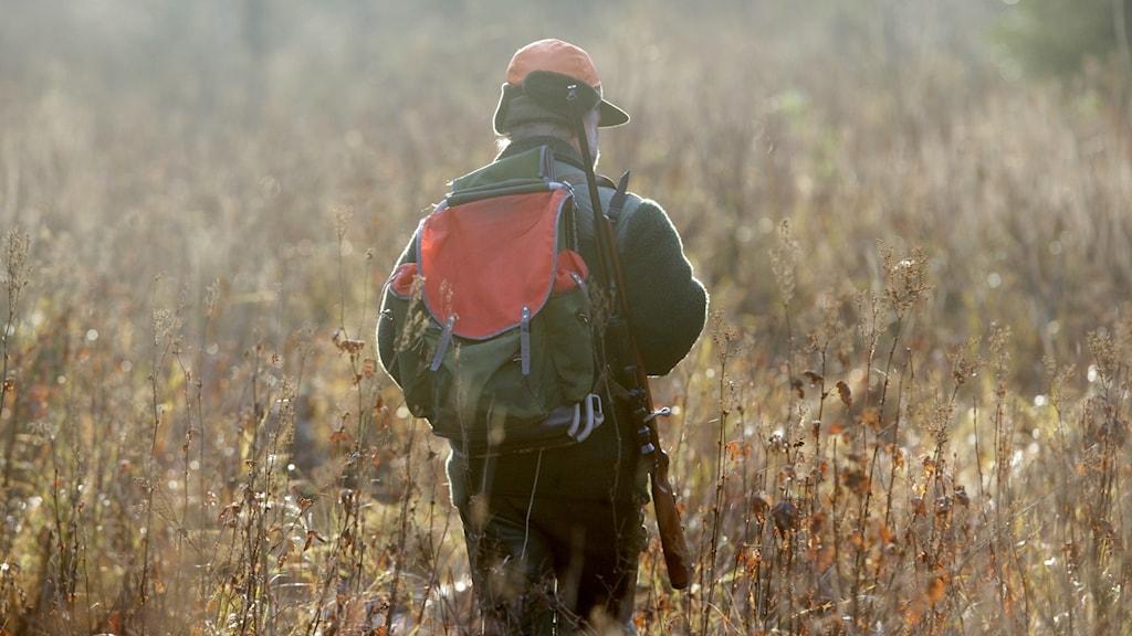 Älgjägare med geväret på axeln.