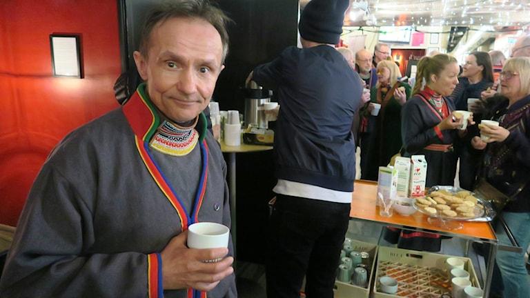 Håkan Jonsson med kaffe i handen i foajen.