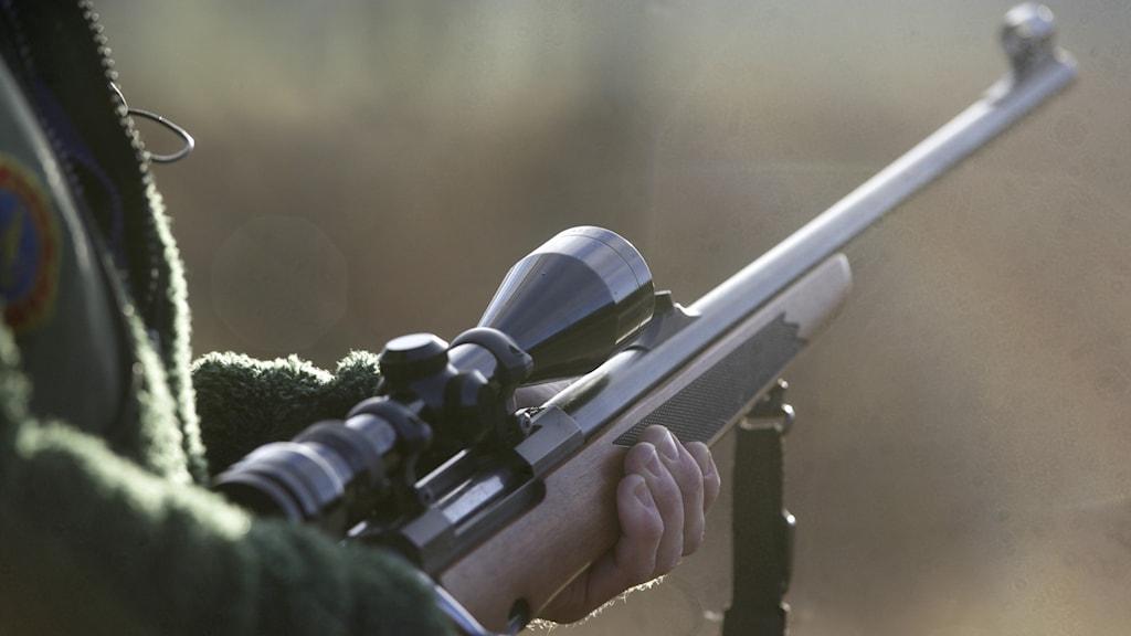 Närbild person i grön jacka håller i ett gevär med kikarsikte i skogen
