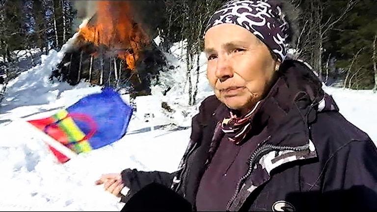 Anita Gimvall med den samiska flaggan framför sin brinnande kåta