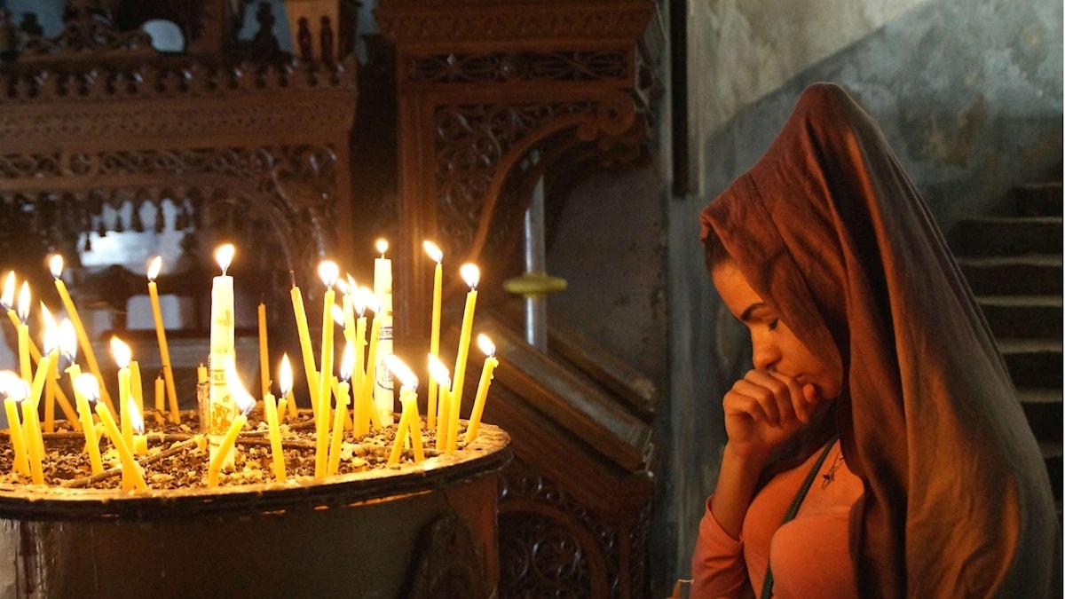Kvinna ber vid ljusbärare