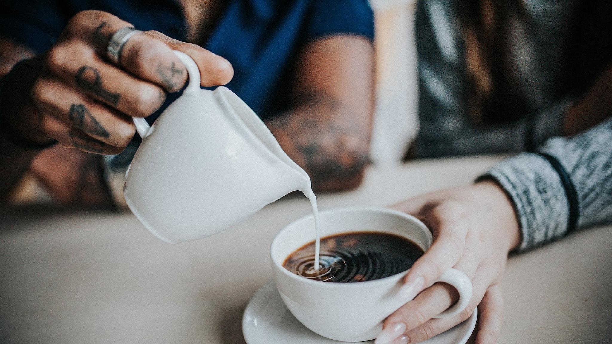 Kaffe, en hand häller upp mjölk
