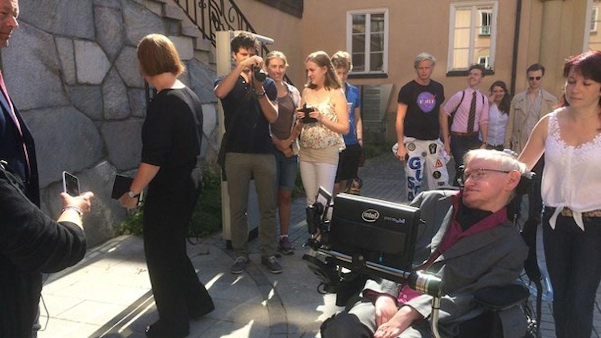 Stephen Hawking i sin rullstol, med andra människor omkring i solsken.
