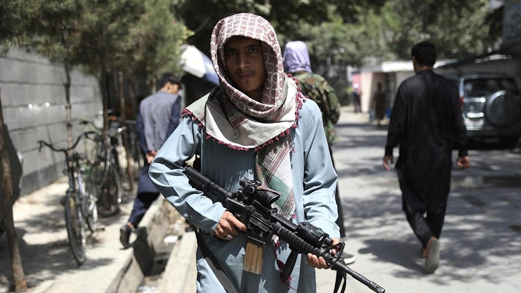 Man med turban och vapen i händerna på gata.