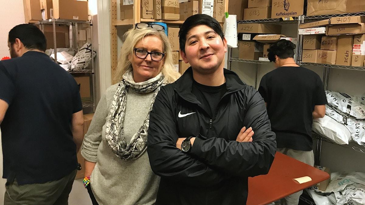 Viktoria Sterner och Hassan Bagheri i butikens paketlager där ryggarna på två medarbetare syns. Foto: Laila Carlsson/Sveriges Radio.