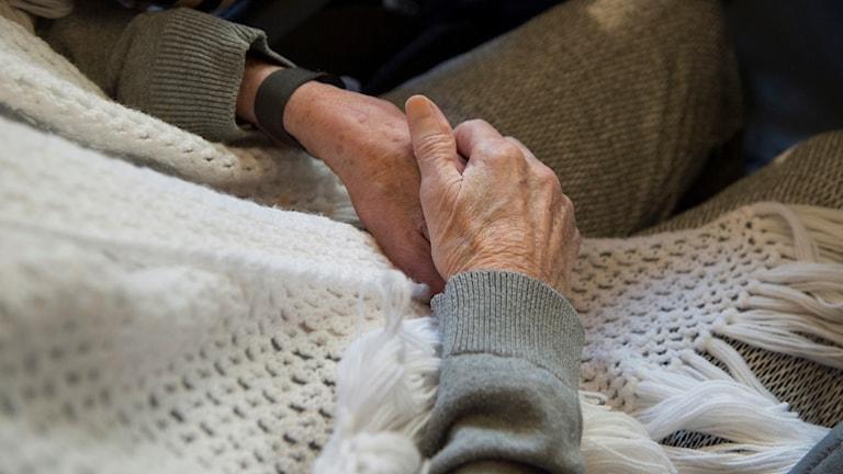 Bilden visar händer och fötter på en äldre person som sitter på en stol.