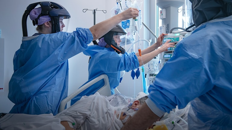 Sjukvårdspersonal i skyddskläder tar hand om en patient på IVA på Södertälje sjukhus.