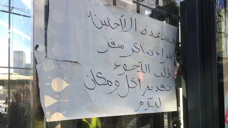 """Malmö central. En skylt där det står """"Vi hjälper flyktingarna med att köpa biljett, lämna asylansökan, mat och sovplatser"""". Foto: Rafand Ahmad/SR."""