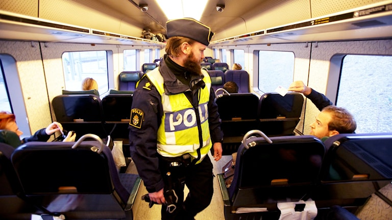 MALMÖ 2015-11-13 En polis kontrollerar id-handlingar på ett Öresundståg mellan Danmarik och Sverige. Foto: Stig-Åke Jönsson / TT kod 70040