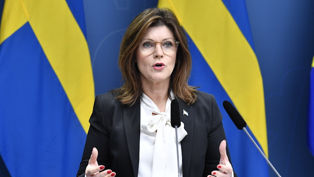 A female member of parliament speaks at a press conference in front of Swedish flags.