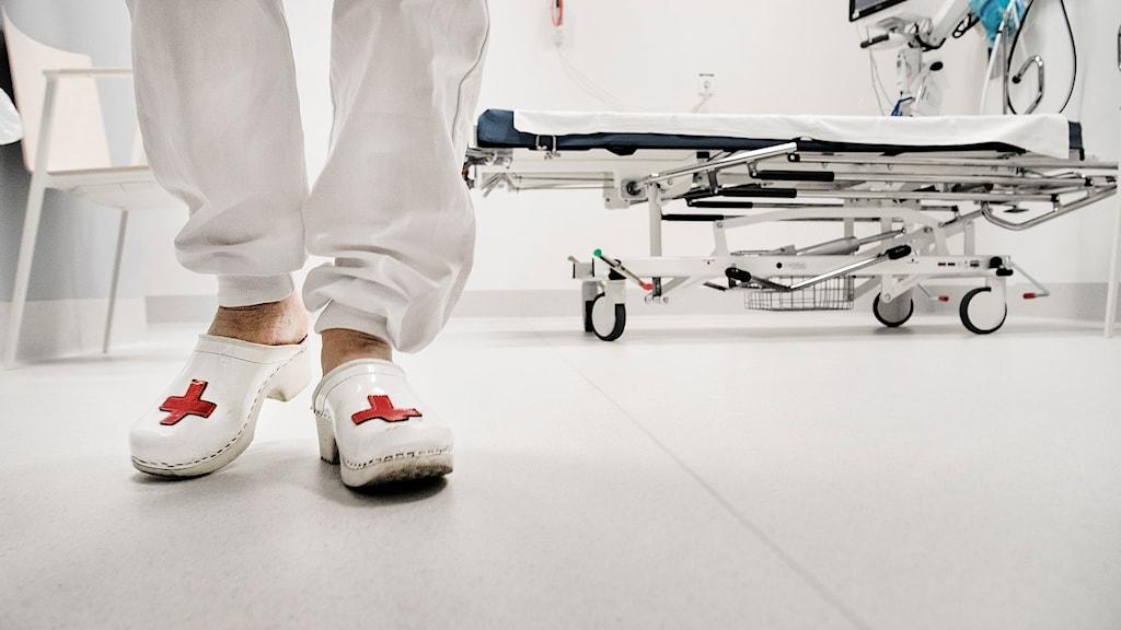 Ett par fötter med vita sjukhustofflor med röda kors på, i sjukhusmiljö.