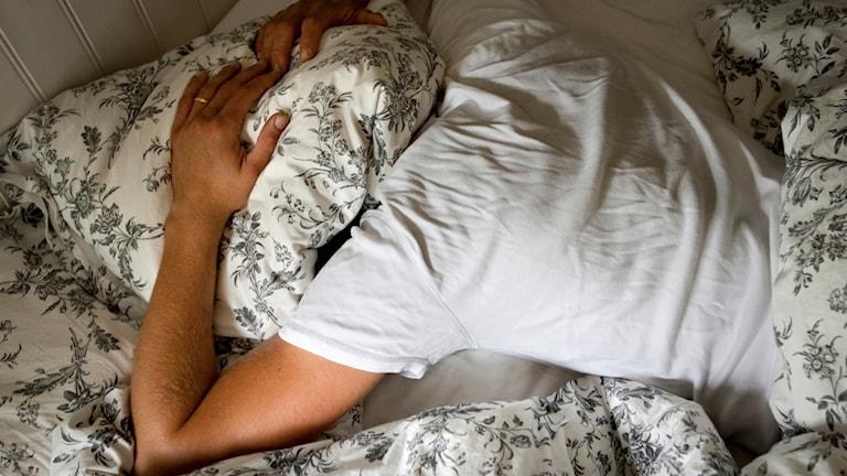 Person med kudde över huvudet i en säng.