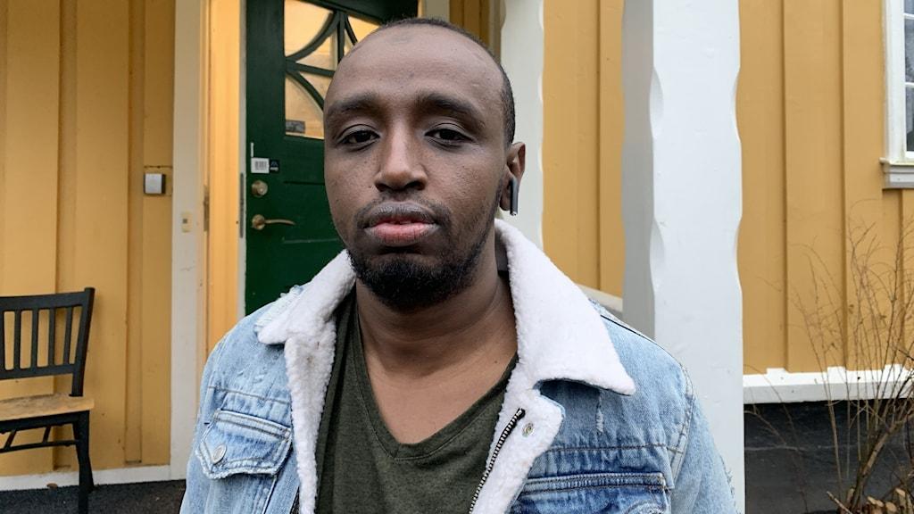 Abdirisak Ahmed tittar in i kameran framför ett gult hus.