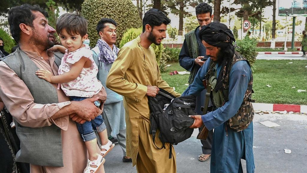En man genomsöker en persons väska, vid sidan av står en man med ett litet barn i famnen.