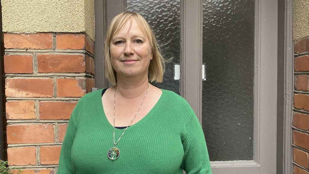 Ann-Sofie Gustavsson står framför en grå dörr med stora glasfönster. Hon är klädd i en grönrandig topp och har ett stort halsband på sig.