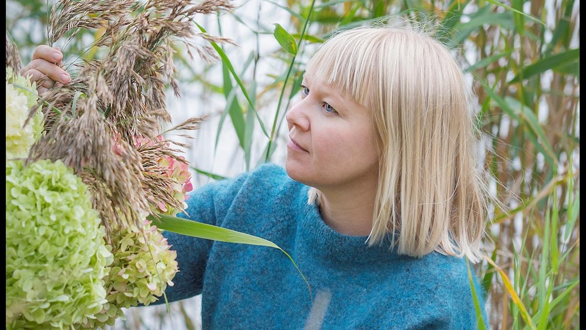 Vaaleatukkainen Hanna Piippo turkoosissa neuleessa, kaislikon keskellä katsoo pitelemäänsä kukka-asetelmaa. Foto: Patrick Miller
