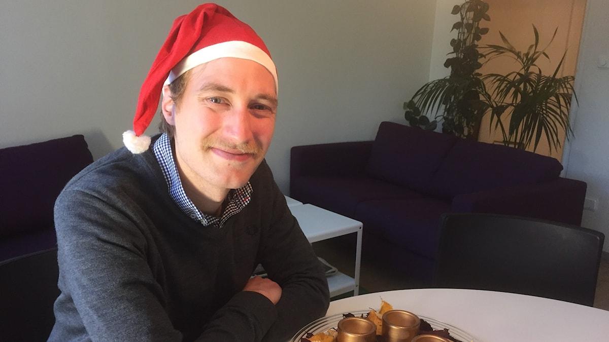 Juontaja Timo Laine istuu hymyillen tonttuhattu päässä nojaillen pöytään kahvihuoneessa. Kuva/Bild: Kirsi Blomberg/SR Sisuradio.
