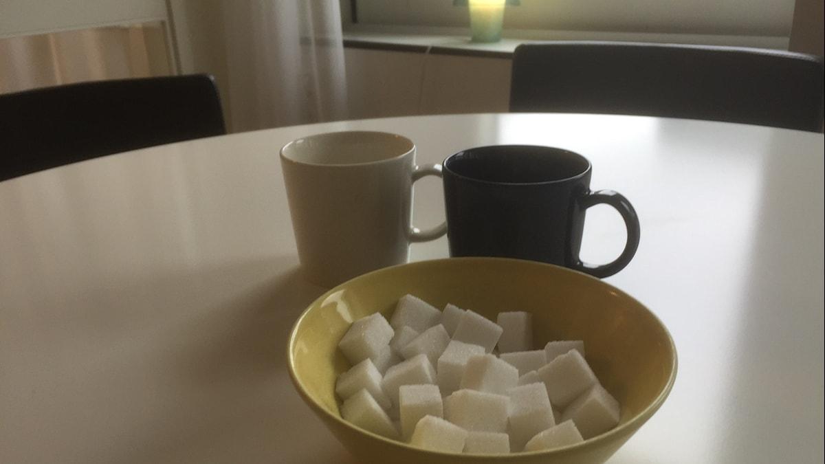 Keltainen kulho, jossa sokeripaloja pöydällä takanaan sininen ja valkoinen kahvikuppi. Kuva: Timo Laine/Sveriges Radio Sisuradio