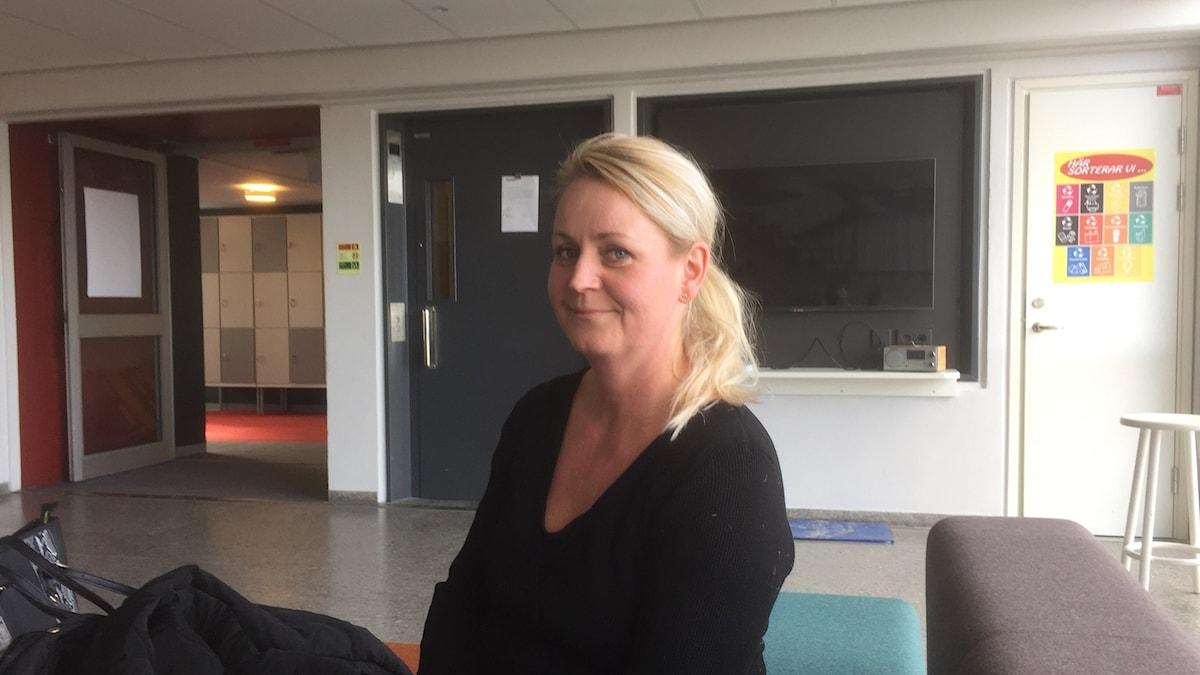 Vaaleahiuksinen Laura Valkonen istuu sivuttain katsoen hymyillen kameraan. Kuva: Timo Laine/Sveriges Radio Sisuradio