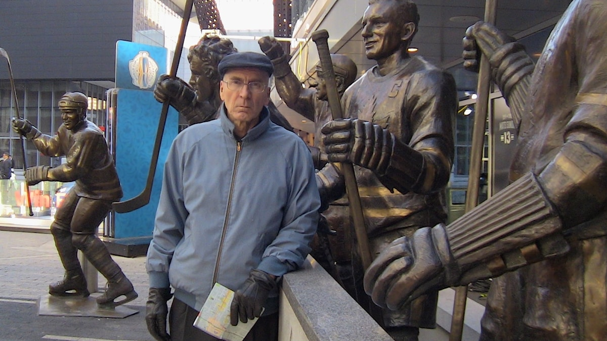 Mies seisoo jääkiekkoareenan edessä olevien jääkiekkoilijapatsaiden edessä. Kuva: Yksityinen